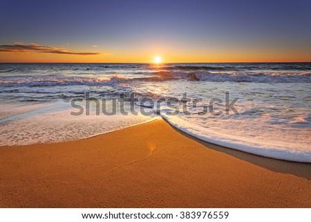 Brilliant ocean beach sunrise. - stock photo