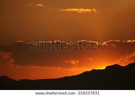 Brilliant orange sunrise over clouds. - stock photo
