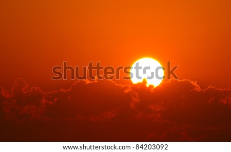 Brilliant orange sunrise over clouds in Iowa with bright yellow sun on a cool spring morning. - stock photo