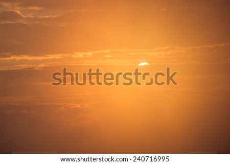 Brilliant orange sunrise over clouds on a cool spring morning - stock photo