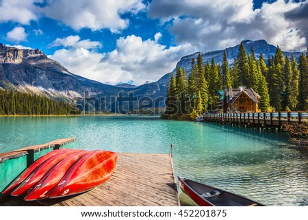 Brilliant red kayaks dry upside down. Emerald Lake in Canadian Rockies. Concept of active vacation and tourism