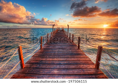 Brilliant sunrise on a sea pier with azure waters  - stock photo