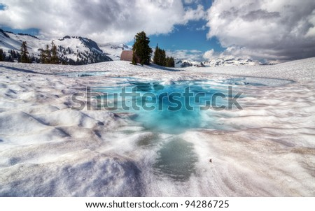 Brilliantly blue melt pool on top of snow - stock photo