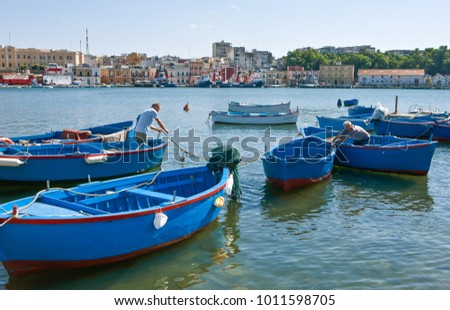 Brindisi, Italy - September 1, 2006: Fishermen  in the large port basin of the city