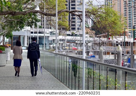 BRISBANE, AUS - SEP 25 2014: Couple walks towards Eagle Street Pier.It is an iconic waterfront precinct with world class dining options and unrivaled views of the Brisbane River. - stock photo