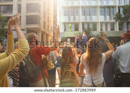 BRISBANE, AUSTRALIA - APRIL 25 : Crowds begin taking photos of marchers in the Anzac day centenary commemorations April 25, 2015 in Brisbane, Australia - stock photo