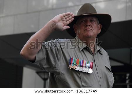 BRISBANE, AUSTRALIA - APRIL 25 : Veteran salutes during march as part of  Anzac day commemorations  April 25, 2013 in Brisbane, Australia - stock photo