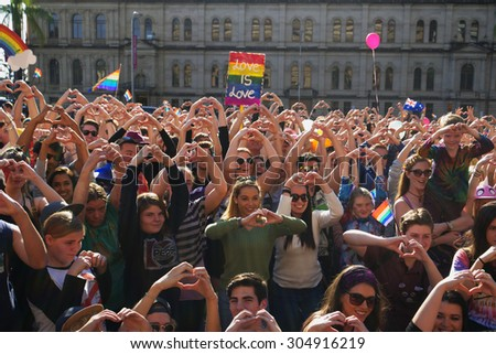BRISBANE, AUSTRALIA - AUGUST 8 2015: Crowds making love heart hand sign at Marriage Equality Rally