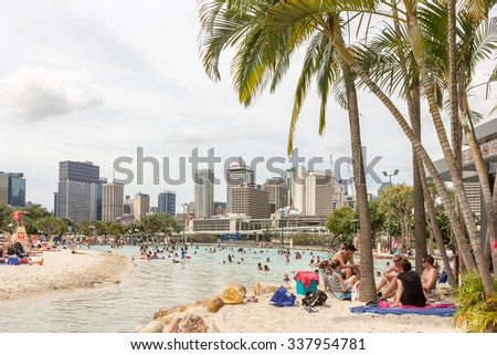 BRISBANE, AUSTRALIA - December 25, 2013:Visitors at Streets Beach in South Bank Parkland. Australia inner-city, man-made beach with Brisbane City Skyline skyscraper Background - stock photo