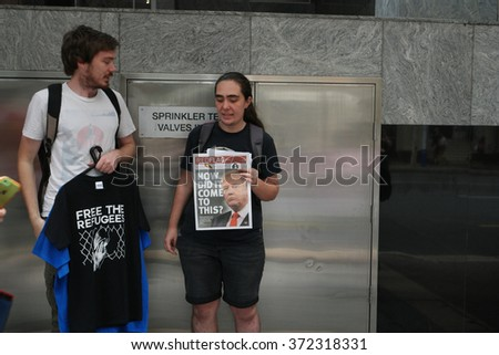 BRISBANE, AUSTRALIA - FEBRUARY 05 : Anti right wing newspaper and t shirt seller at protest in support of churches offering sanctuary to refugees February 05, 2016 in Brisbane, Australia - stock photo
