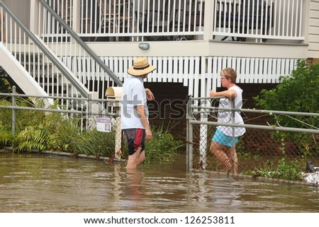 BRISBANE, AUSTRALIA - JANUARY 28 : Unidentified residents chat in flood waters from ex tropical cyclone Oswald on January 28, 2013 in Brisbane, Australia - stock photo
