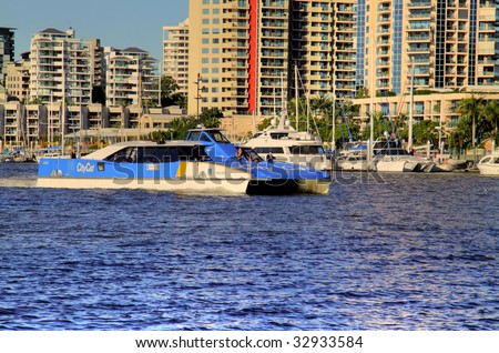 BRISBANE, AUSTRALIA - June 17: City cat passes by riverfront apartment towers in Brisbane, Australia on June 17, 2009. The city cat ferry service began in 1996 and now has 13 vessels. They are named after Aboriginal place names. - stock photo
