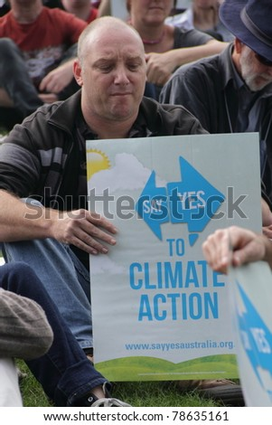 BRISBANE, AUSTRALIA - JUNE 6 : man with say Yes to climate action sign listening to rally speakers during World Environment Day say Yes protest 6, 2011 in Brisbane, Australia - stock photo