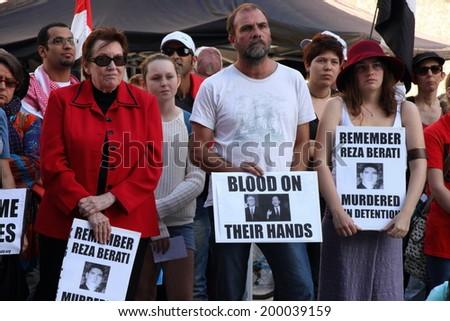 BRISBANE, AUSTRALIA - JUNE 22 : Unidentified protesters holding anti liberal government and reza berati remembrance signs  attending World Refugee Rally June 22, 2014 in Brisbane, Australia - stock photo