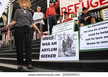 BRISBANE, AUSTRALIA - JUNE 22 : Unidentified protesters holding Christian protest signs whilst at World Refugee Rally June 22, 2014 in Brisbane, Australia