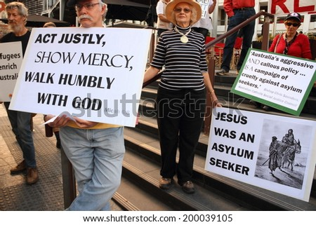 BRISBANE, AUSTRALIA - JUNE 22 : Unidentified protesters holding Christian protest signs whilst at World Refugee Rally June 22, 2014 in Brisbane, Australia - stock photo