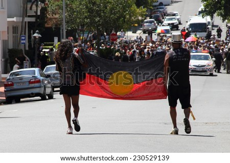 BRISBANE, AUSTRALIA - NOVEMBER 14 : Unidentified protestors  carrying flag to marchers in Musgrave Park gate opening ceremony at g20 aboriginal protest on November 14, 2014 in Brisbane, Australia - stock photo