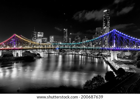 BRISBANE, AUSTRALIA: Story Bridge by Night - multi-coloured lights (Pink, Yellow, Green, Purple) with black and white city