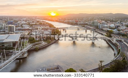 Brisbane City, Beautiful Panorama Aerial View of Kurilpa Bridge, William Jolly Bridge and Merivale Bridge over Brisbane River with Cityscape under Golden Sky at Sunset in Summer, Queensland, Australia - stock photo