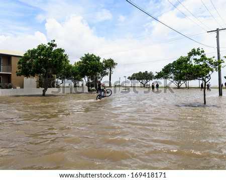 BRISBANE, QLD, AUSTRALIA - January 27: A man on a bicycle does a wheelie in the flooded street in Sandgate in the floods of 27 January 2013 - stock photo