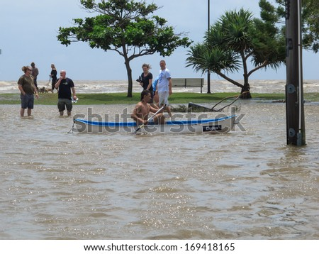 BRISBANE, QLD, AUSTRALIA - January 27: A man rows past in a canoe as locals explore the flooded streets of Sandgate during the storm surge floods of 27 January 2013 - stock photo