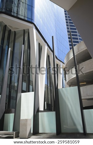 BRISBANE, QLD, AUSTRALIA - MARCH 17, 2014: view to steel concrete and glass  commercial modern building exterior with fence and round parking on riverside in Brisbane, QLD, Australia on March 17, 2014 - stock photo