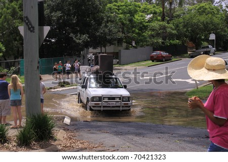 BRISBANE, QUEENSLAND/AUSTRALIA - JANUARY 13: Car driving through flooded street on January 13, 2011 in Toowong, Brisbane, Queensland, Australia. - stock photo