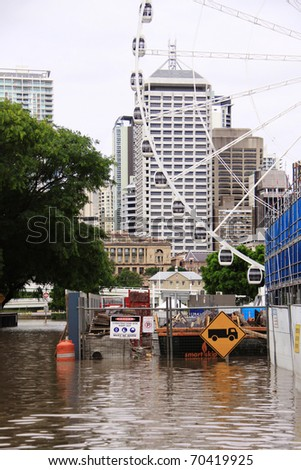 BRISBANE, QUEENSLAND/AUSTRALIA - JANUARY 13: Flooded area in front of the Brisbane Ferris wheel on January 13, 2011 in Toowong, Brisbane, Queensland, Australia. - stock photo