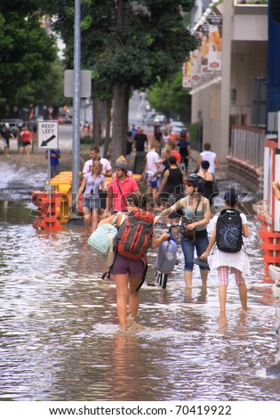 BRISBANE, QUEENSLAND/AUSTRALIA - JANUARY 13: People walking through flooded streets on January 13, 2011 in South Bank, Brisbane, Queensland, Australia. - stock photo