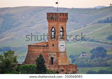 Brisighella clock tower with green hill in the background - stock photo