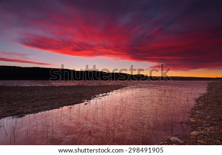 Brisk and windy winter sunset sky and reflections over Lake Burralow in Penrith, Australia - stock photo