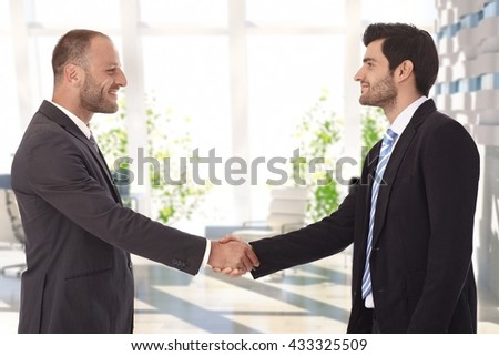Bristly caucasian businessmen shaking hands on successful deal at bank center lobby. Smiling, standing, wearing suit and tie. - stock photo