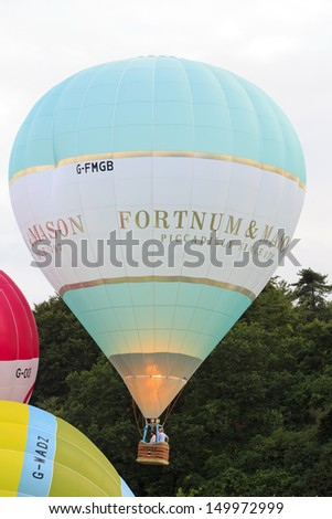 BRISTOL, ENGLAND - AUGUST 10: Fortnum & Mason balloon takes off at the 6pm mass ascent at the Bristol International Balloon Fiesta, England, August 10, 2013 - stock photo