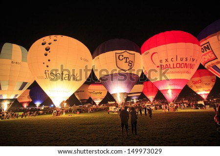 BRISTOL, ENGLAND - AUGUST 10: The Night Glow, sponsored by Airbus, beautifully lights up the skies, all set to a soundtrack at the Bristol International Balloon Fiesta, England, August 10, 2013 - stock photo