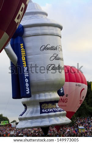 BRISTOL, ENGLAND - AUGUST 10: The Scottish Football Association Challenge Cup, Sponsored by William Hill, balloon takes off at the mass ascent at the Bristol Balloon Fiesta, England, August 10, 2013 - stock photo
