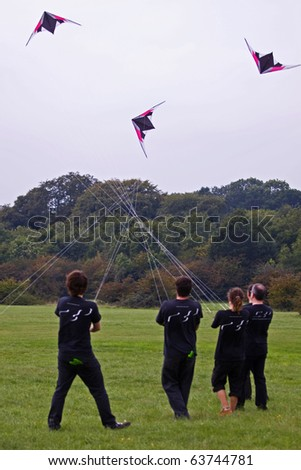 BRISTOL, ENGLAND - SEPTEMBER 4: Members of a kite flying team coping with a strong wind at the International Kite Festival  on September 4, 2010 in Bristol, England. - stock photo