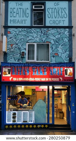 BRISTOL - MAY 18: View of a graffiti piece on a shop front in the Stokes Croft area on May 18, 2015 in Bristol, UK. Bristol is famous for its vibrant graffiti and street art. - stock photo