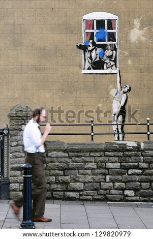 BRISTOL - NOV 7: The famous Banksy graffiti piece 'Naked Man' seen on a building in the city centre on Nov 7, 2010 in Bristol, UK. Banksy is an internationally renowned street artist from Bristol. - stock photo