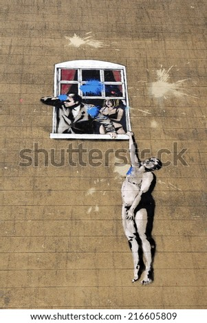 "BRISTOL - NOV 8: View of a graffiti piece named ""Naked Man"" by street artist Banksy on a city centre wall on Nov 8, 2010 in Bristol, UK. Banksy is an internationally acclaimed artist from Bristol. - stock photo"