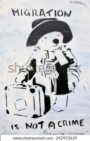 BRISTOL - SEP 26: View of Paddington Bear migration themed graffiti by street artist Banksy on a city centre wall on Sep 26, 2010 in Bristol, UK. Immigration policy is a reoccurring topic in the UK. - stock photo