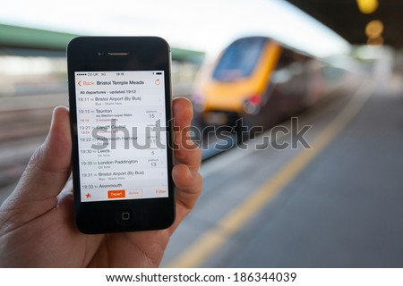 BRISTOL, UK - APRIL 8, 2014: A male hand holding an iPhone at Bristol railway station with a train in the background. The smart phone displays live train travel information on the Train Times App. - stock photo