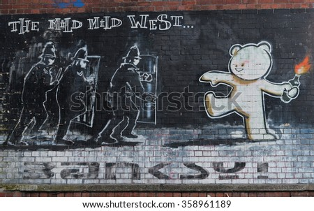 BRISTOL, UK - MAY 18, 2015: View of the famous Banksy graffiti piece titled Mild Mild West seen on a city centre brick wall. Bristol is well known for its vibrant and political street art scene.