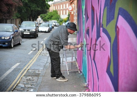 BRISTOL, UK - SEP 21, 2012: A graffiti artist works on a wall in the Stokes Croft area of the city. The west country city is internationally renowned for its vibrant street art and graffiti scene. - stock photo