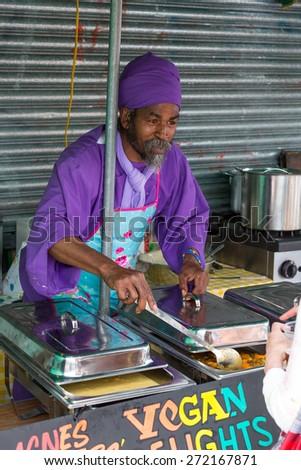 Bristol, UK. 5th July 2014. Man serving Vegan Delights - stock photo