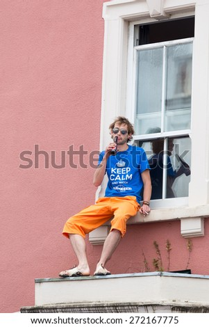 Bristol, UK. 5th July 2014. Man watching St Paul's Carnival from a first floor window relaxes with a beer - stock photo
