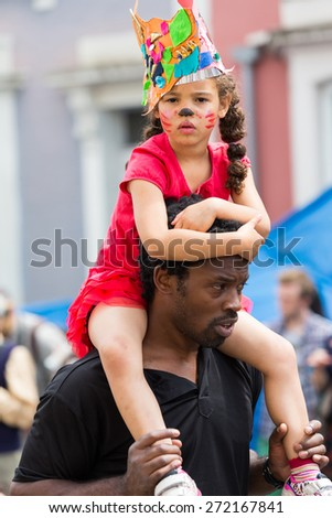 Bristol, UK. 5th July 2014. Young girl enjoys the view from her father�¢??s shoulders - stock photo