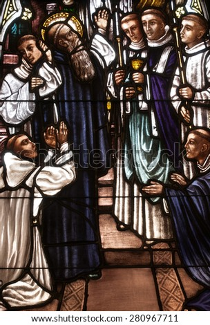 BRISTOW, VIRGINIA - APRIL 26, 2015: Stained glass window depicting the death of St. Benedict of Nursia surrounded by his monks, located in chapel of St. Benedict Monastery - stock photo