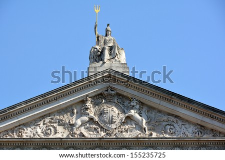 Britannia statue with Trident and Coat of arms below at roof level on Somerset House London - stock photo