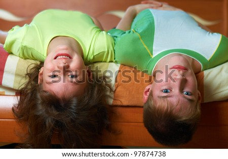 Brither and sister lying in bed up side down