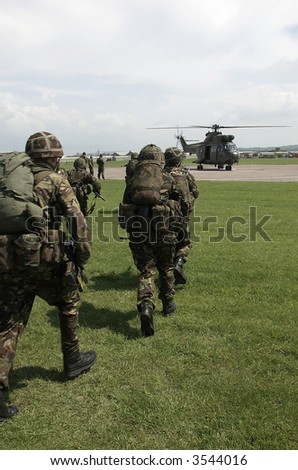 British Army soldiers board helicopter - stock photo